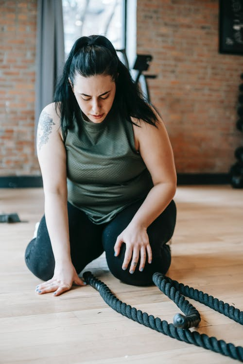 Full body concentrated plus sized female in activewear sitting on floor and exercising with battling ropes in modern gym