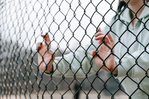 Crop unrecognizable woman touching net fence on street