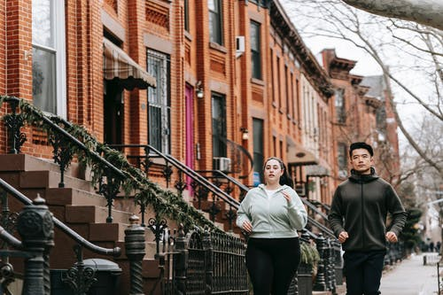 Concentrated plump woman and Asian man jogging together along residential street on autumn day
