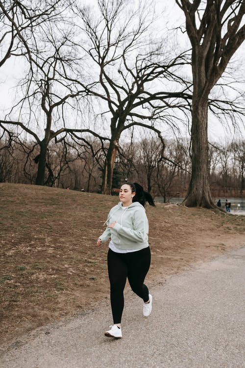 Full body motivated plus sized female in gray hoodie running in autumn park