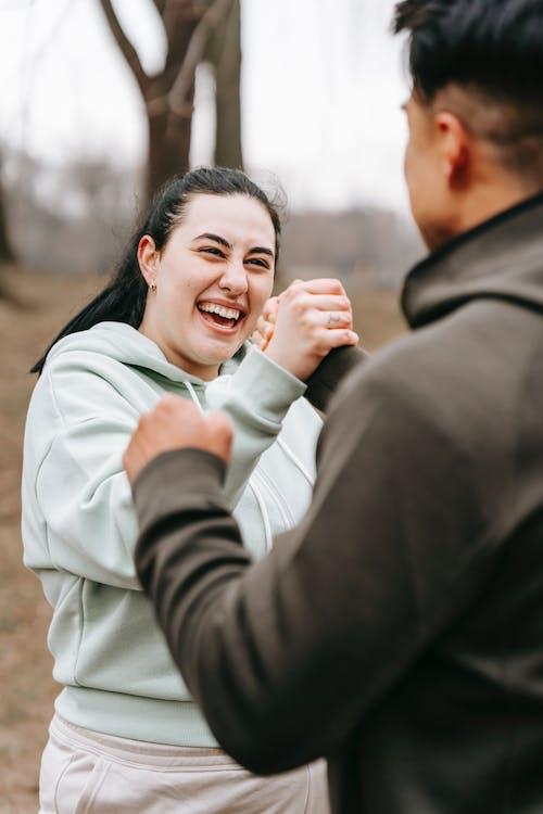 Joyful friends shaking hands in autumn park