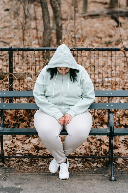 Full body sad plus sized brunette in hoodie sitting on bench in autumn park and looking down