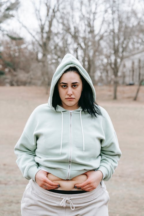 Sad plus sized female in hoodie touching and showing fat on belly while standing in leafless park and looking at camera