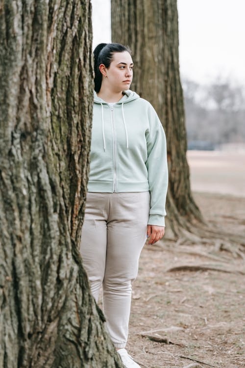Wistful plump woman standing near tree in autumn park
