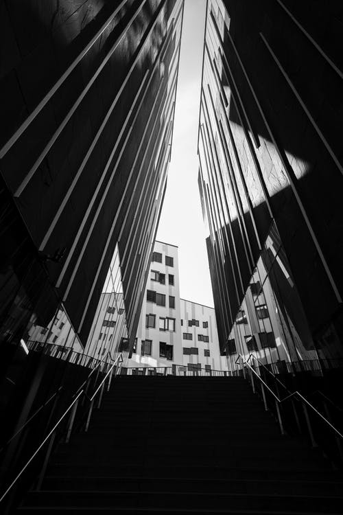 Grayscale Photo of Staircase Between High Rise Buildings