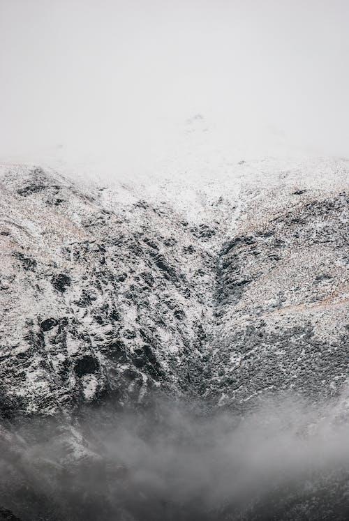 Snowy mountain ridge against misty sky