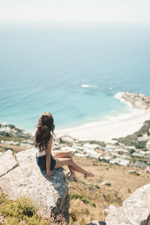 A Woman on a Rocky Cliff with a Scenic View