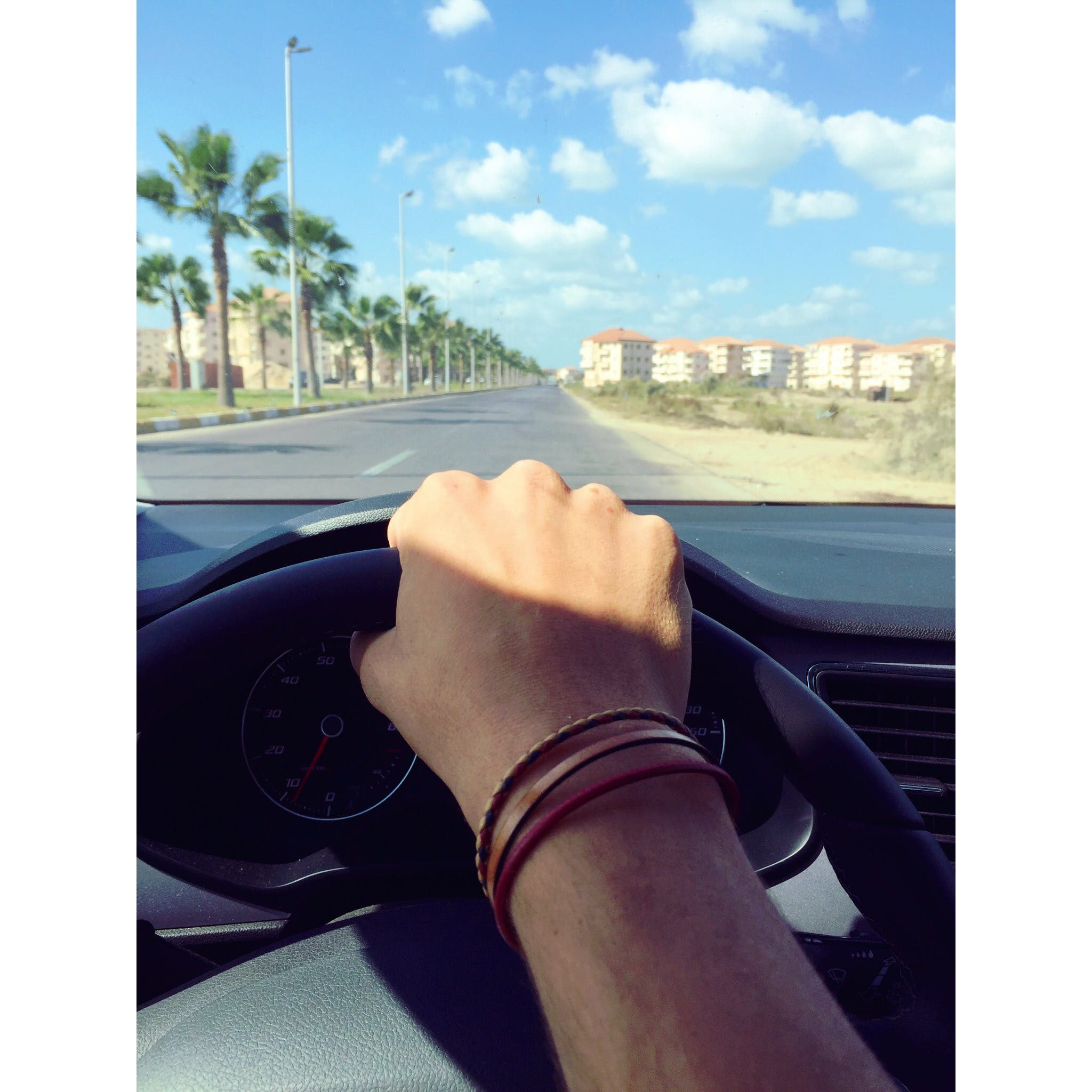 Person Withe Bracelets Holding Black Steering Wheel