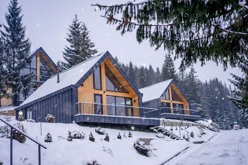 Brown Wooden House Covered With Snow Near Green Trees