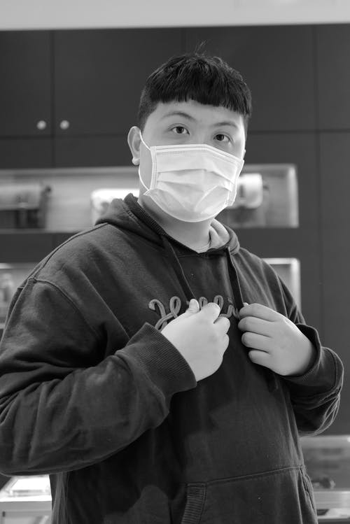 Man in Black Hoodie Wearing White Face Mask and Gloves