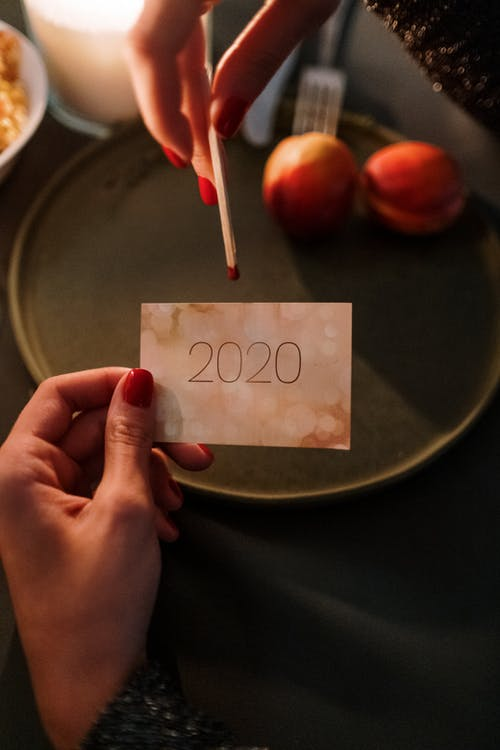 Photo of a Person's Hand Holding a 2020 Card and a Match Stick