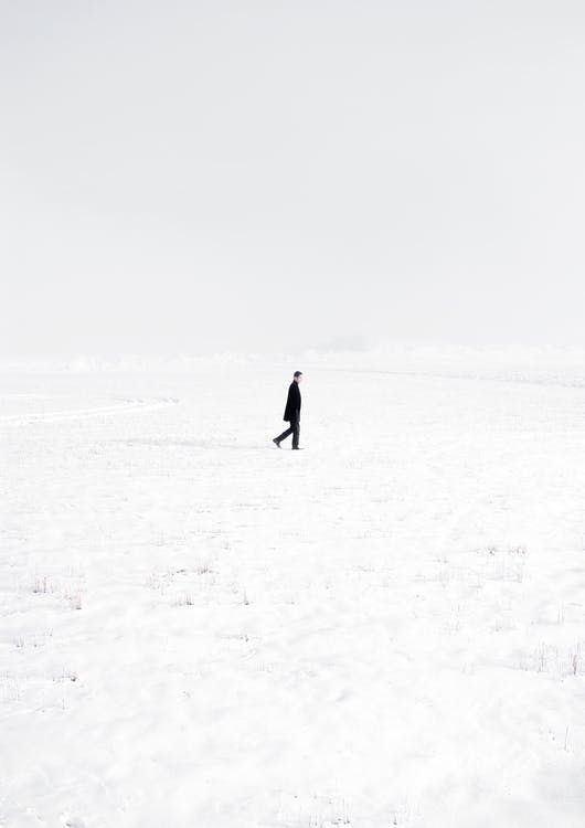 Lonely man in middle of snowy valley
