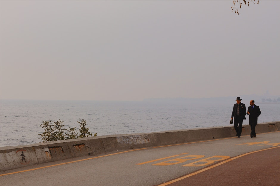Two Person Walking on a Concrete Road Beside Body of Water