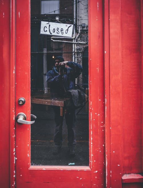 Full body of unrecognizable male traveler in warm casual clothes taking photo of aged red building with closed sign hanging on glass door