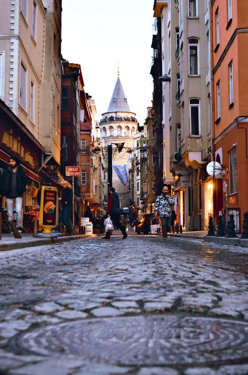 Galata Tower and old multistory buildings with anonymous tourists outdoors