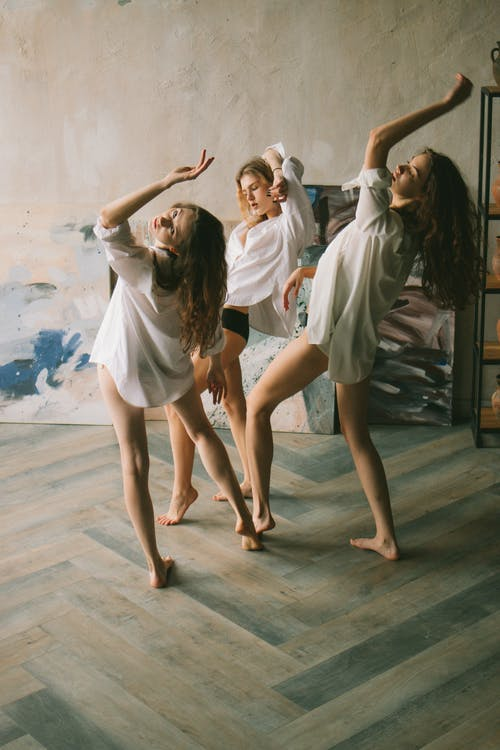 Female friends wearing shirts while dancing in studio