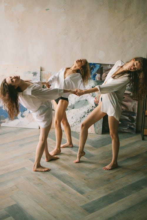 Ladies in shirts dancing near paintings in studio