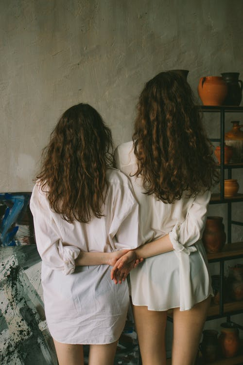 Back view of anonymous ladies wearing white shirts while standing in light studio near painting and shelves with pottery while holding hands
