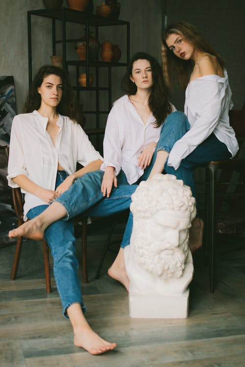 Alluring young women in similar outfits resting in art studio