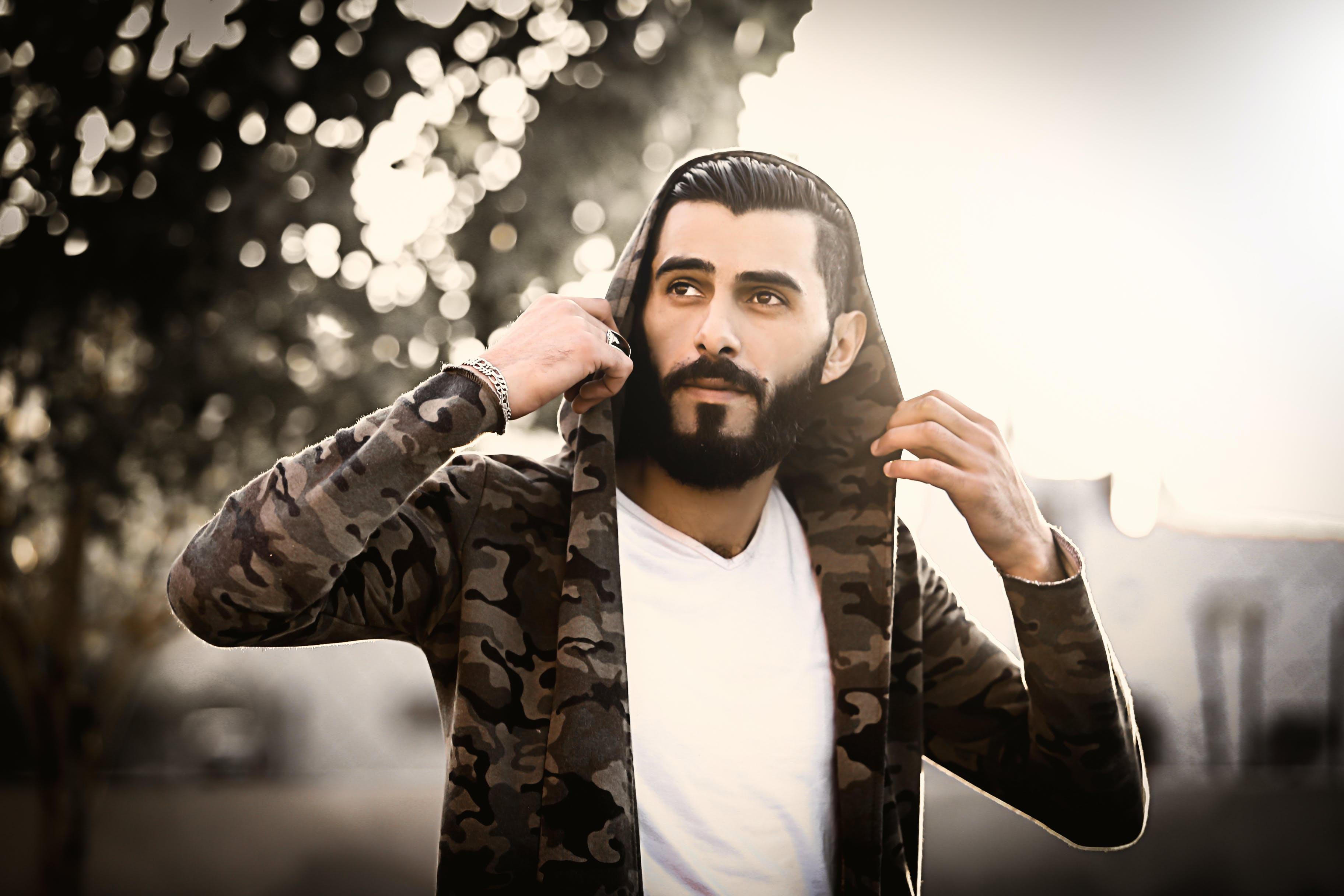 Man Wearing Camouflage Hoodie and White Shirt