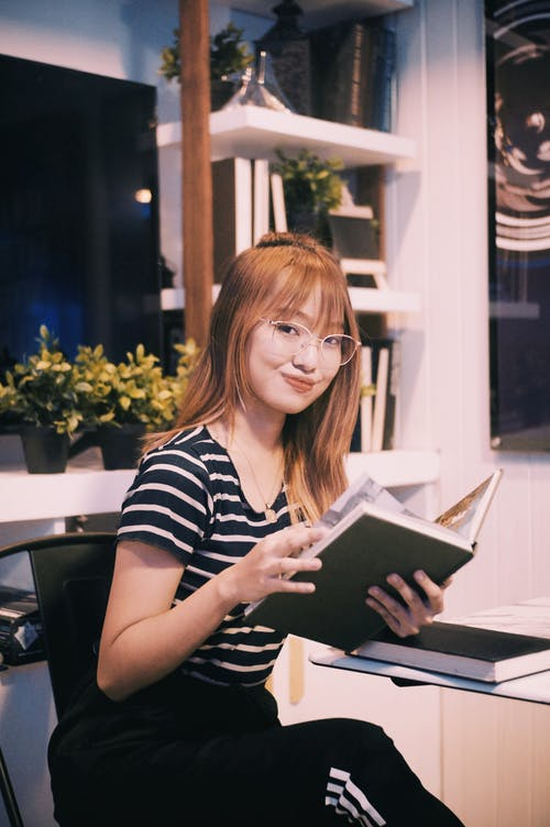 Intelligent cheerful young ethnic female with red hair reading book and looking at camera