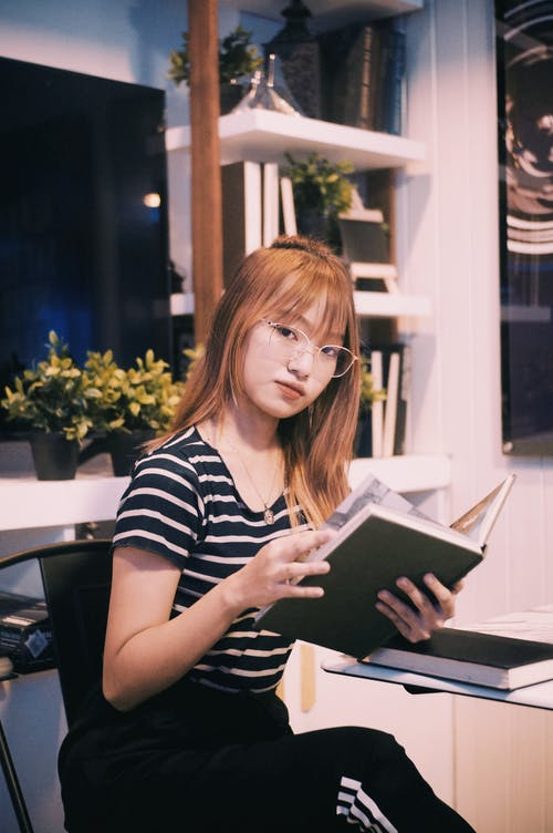Smart young Asian woman in eyeglasses with book