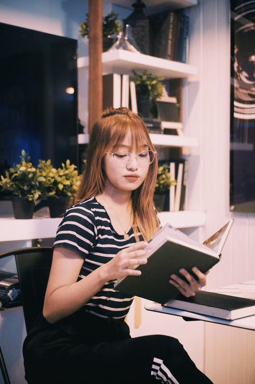 Young clever serious ethnic student with red hair in striped T shirt reading book
