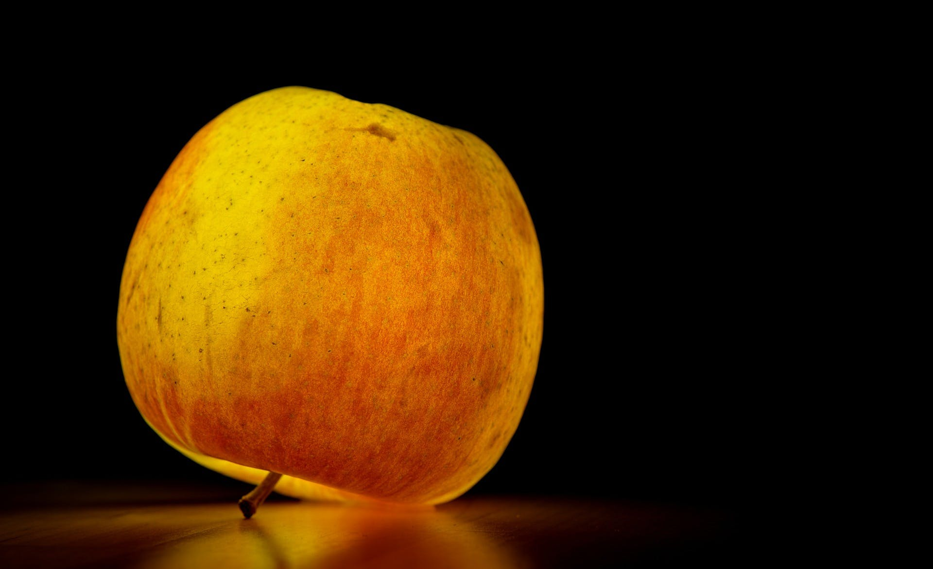 Lighted Apple over Black Surface