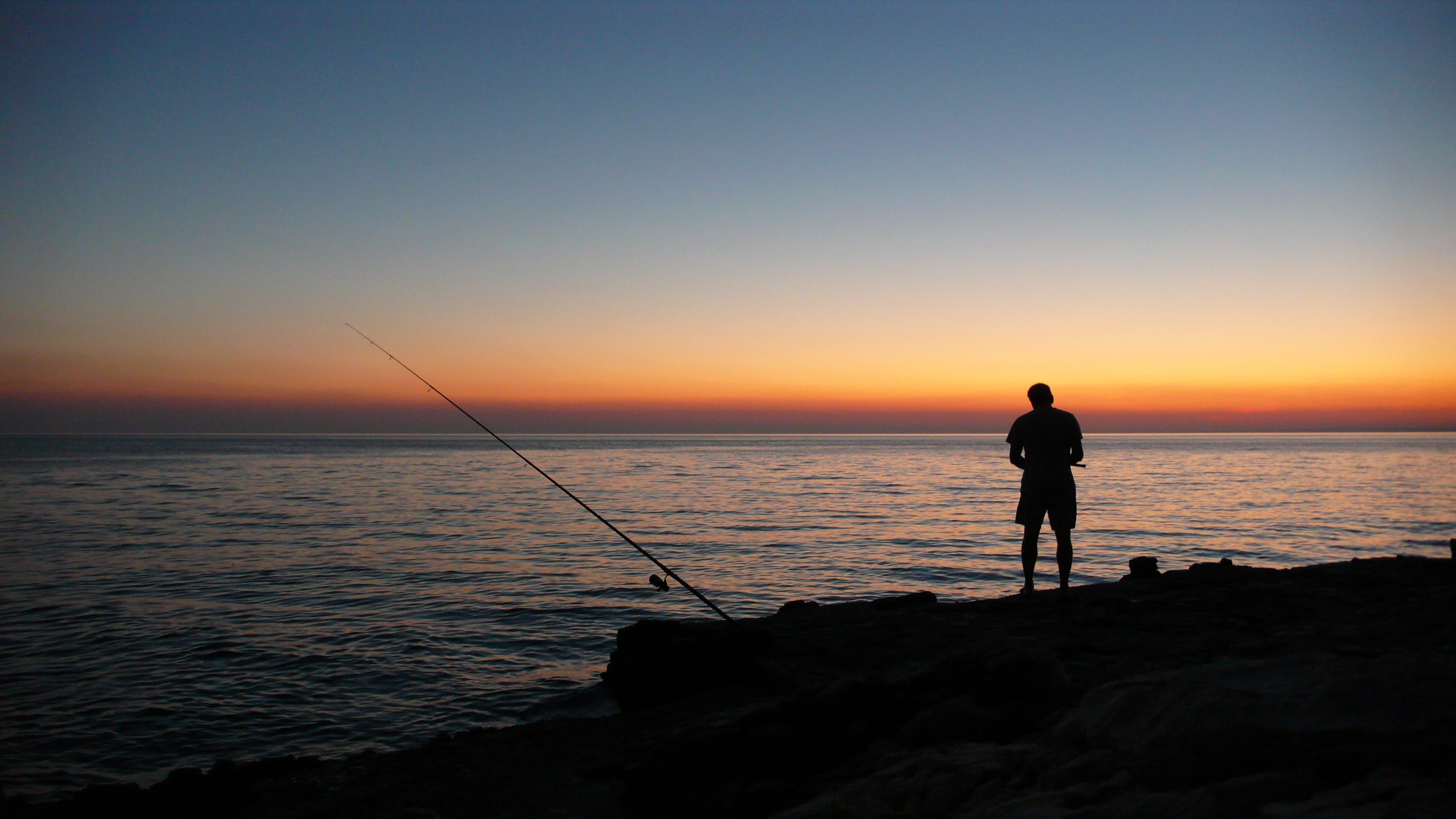 Person Fishing during Sunset