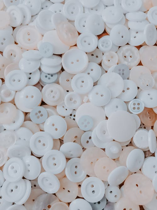 From above of pile pastel colored buttons scattered on table as abstract background
