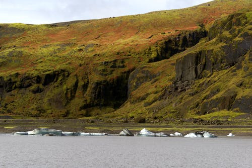 White Boats on Sea Near Brown Mountain