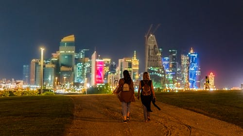Back view of unrecognizable female tourists in casual clothes and backpack walking on sandy road towards modern illuminated buildings in Doha at night