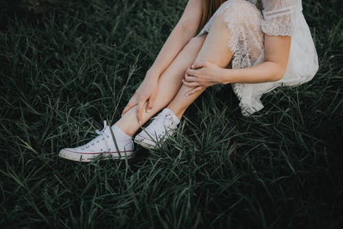 Woman in White Lace Up Sneakers Sitting on Grass Field