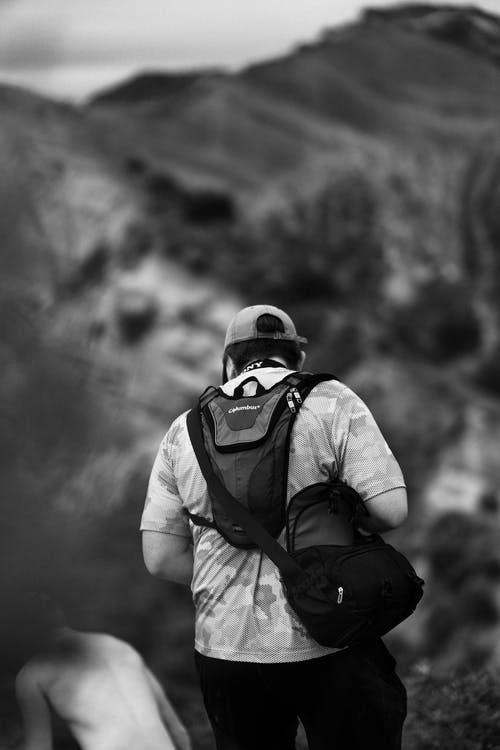 Black and white back view of anonymous male hiker with backpack wearing cap standing against rocky cliff in nature during trekking on blurred background