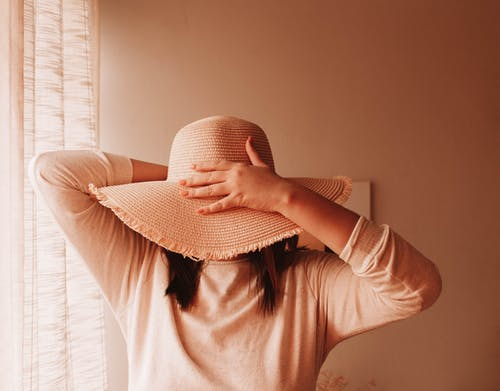 Anonymous female in casual wear covering face with beach hat against beige wall in house on sunny day