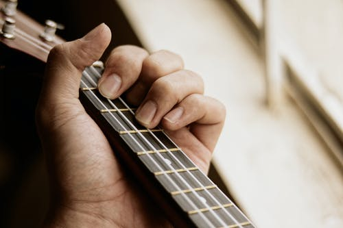 Crop anonymous male musician placing hand on acoustic guitar neck and playing music in light room