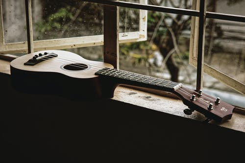 Classic acoustic ukulele placed on narrow windowsill of old rural house in daylight