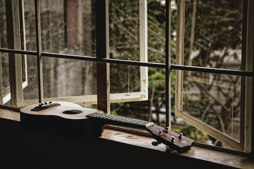 Modern classy acoustic ukulele placed on narrow windowsill in rural house in daylight