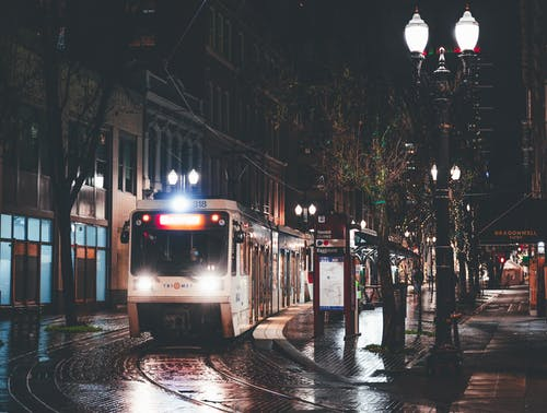 Modern tramway driving on rails on paved road near aged residential buildings in city at rainy night