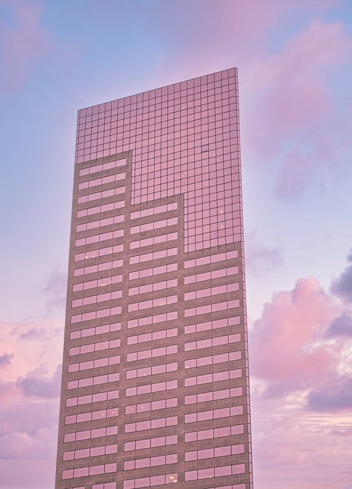 Contemporary skyscraper with glass mirrored facade reflecting sunset sky