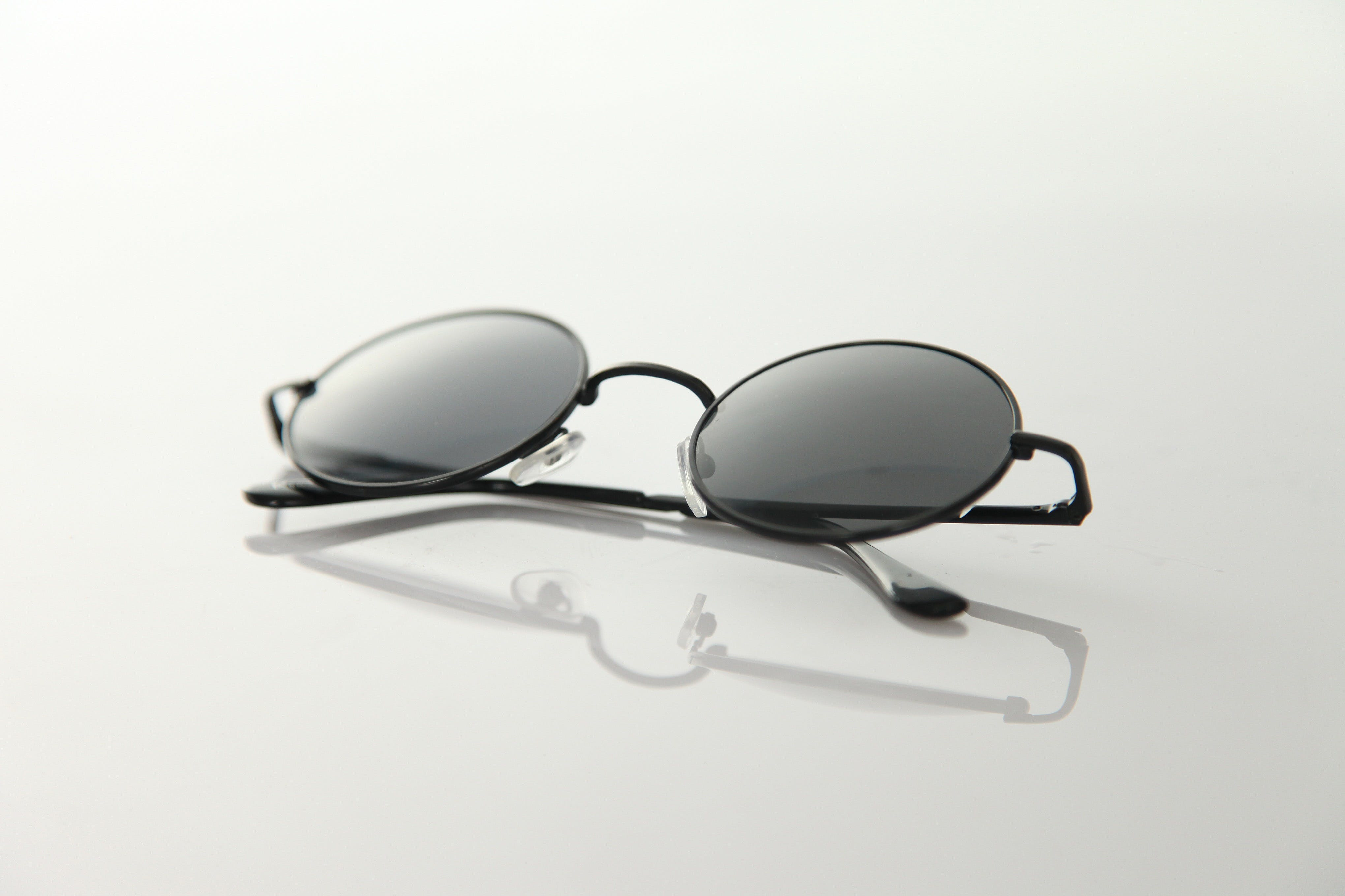 Black Frame Sunglasses on White Surface