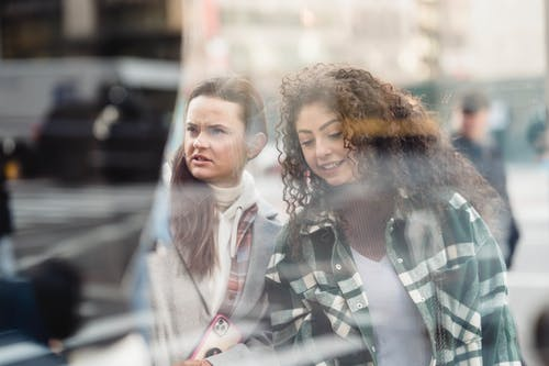 Through glass of content multiracial female friends standing on street near show window of store while choosing goods on blurred background