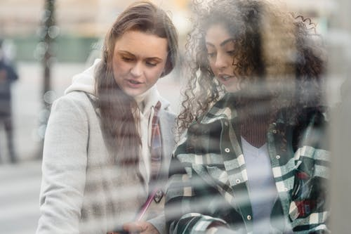 Through glass of multiethnic women at store on street