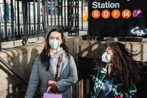 Multiracial female friends with shopping bag in protective masks walking up stairs of subway station on sunny street in city