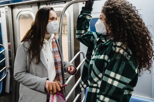 Content multiethnic women in protective masks riding in subway train