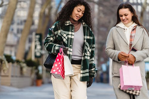 Cheerful diverse women with shopping bags walking on street