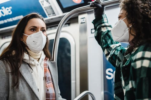 Content diverse female friends wearing outerwear in protective masks riding in subway train together during pandemic while commuting in metro