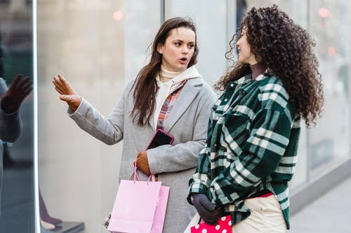 Multiethnic female friends with shopping bags looking at each other and communicating while standing on sidewalk near shop window on street