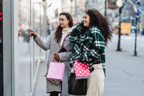 Side view of cheerful multiracial female friends with shopping bags standing on sidewalk near showcase of store on street on blurred background