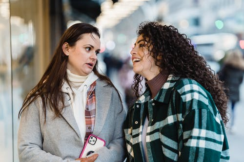 Optimistic multiracial female friends in outerwear chatting while standing near showcase of store on street in city on blurred background